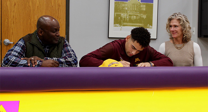 Peter Udoibok signs his U of M paperwork while his proud parents, Kenneth and Meredith, watch.